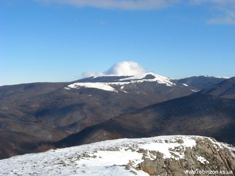 На заднем плане на верхушку горы взгромоздилось большое облако